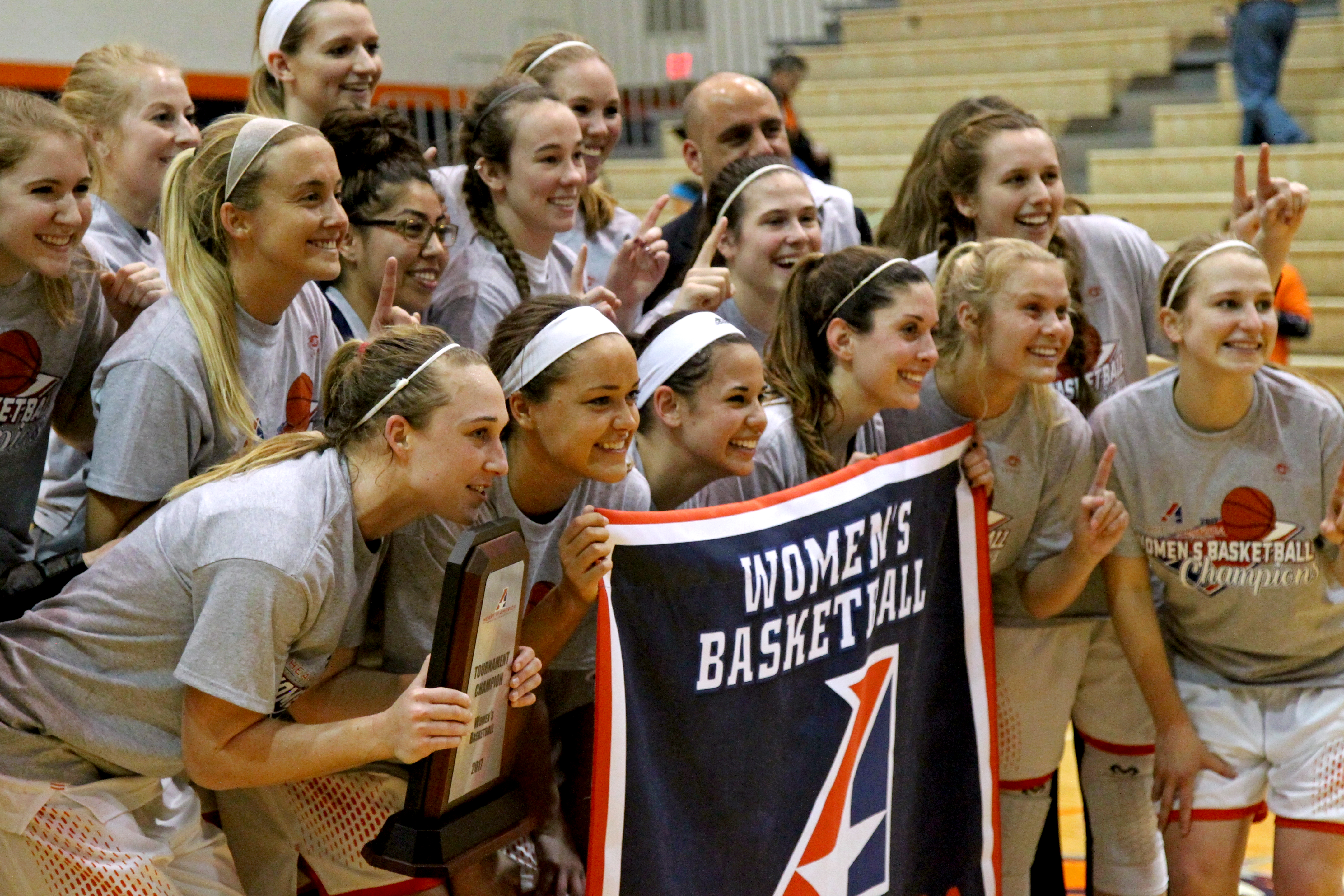 The Baker women's basketball players pose for a photo with their Heart championship banner after defeating Benedictine 64-51. The team won its first-ever Heart Conference Tournament title along with the regular-season championship. Photo by Chad Phillips.