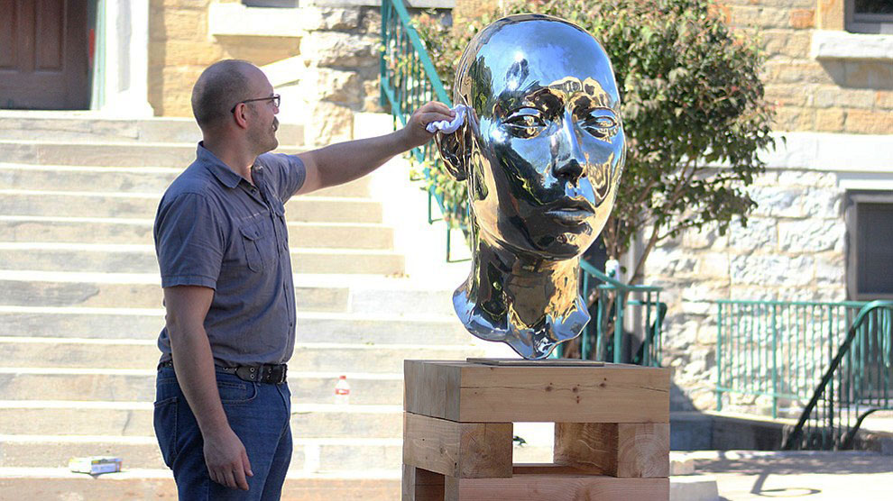 David Platter cleans off his sculpture titled