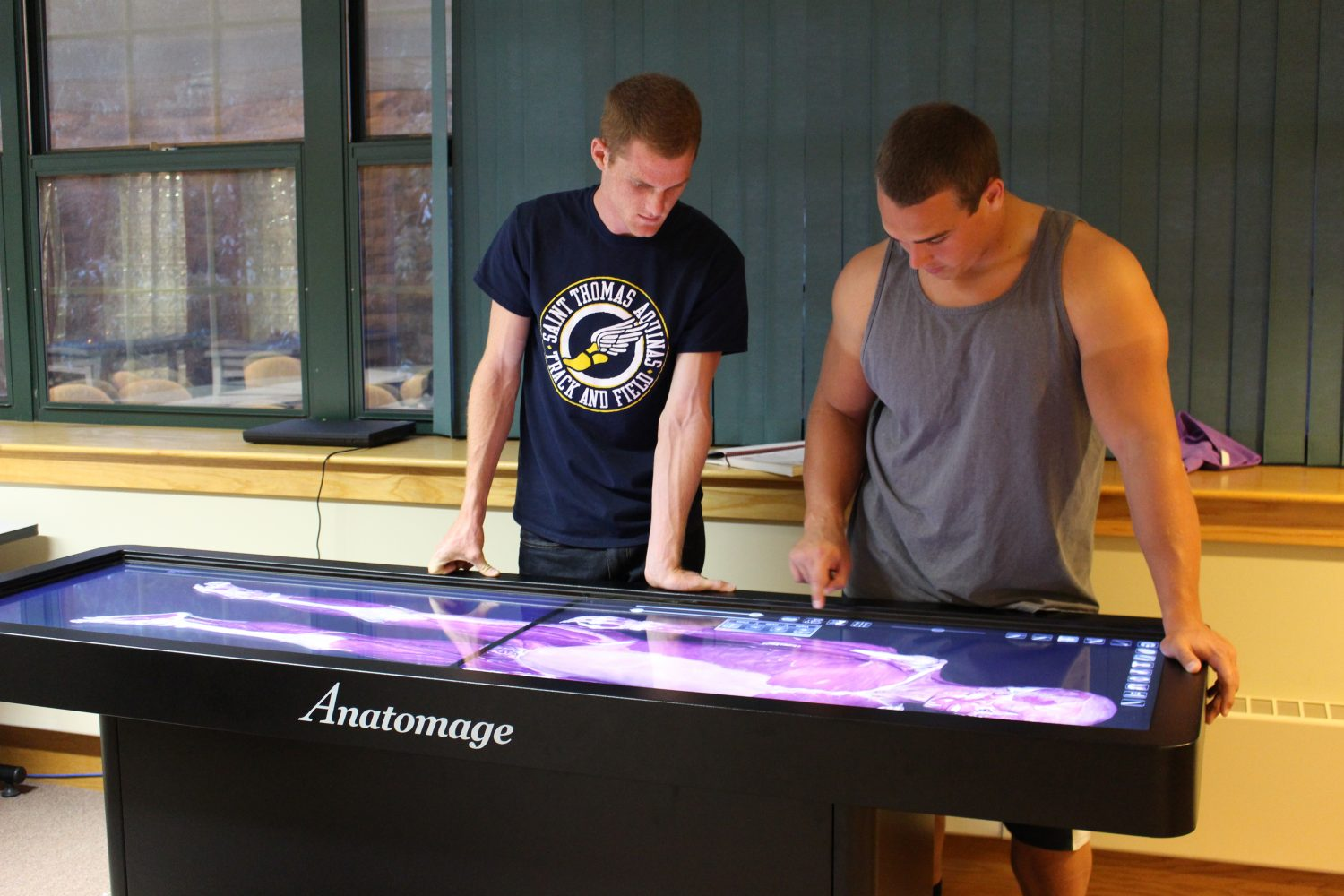 Exercise+Science+students+Joe+Linder+and+Josh+Kock+use+the+Anatomage+table+in+Mabee+Hall.+The+Anatomage+table+replaces+traditional+cadaver+labs.+Image+by+Jenna+Black.