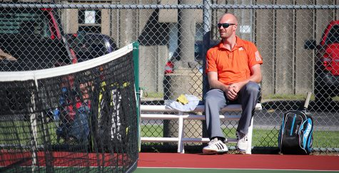 Head tennis coach Keith Pipkin watches a match Oct. 7 against William Jewell College. Pipkin is in his first year at Baker. Image by Jenna Black.