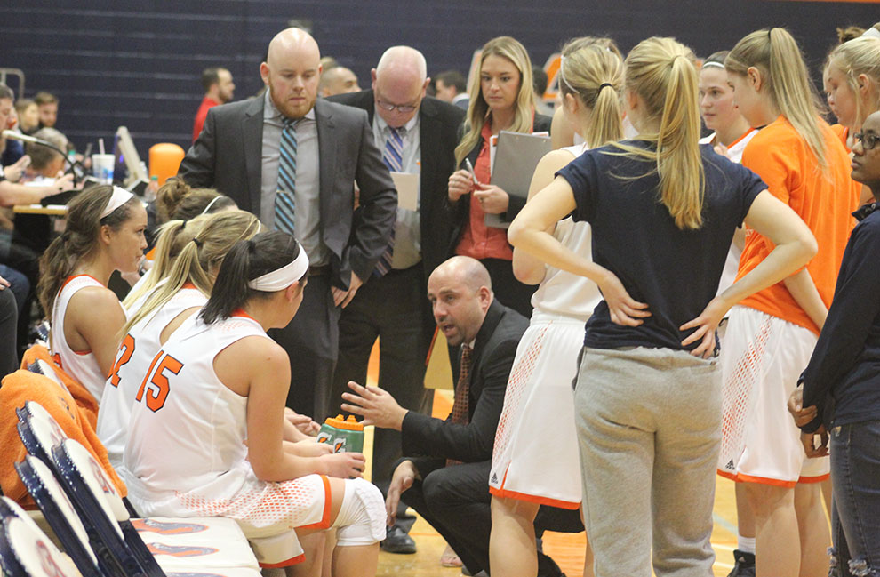 The women's basketball team gathers around coach Ben Lister during a timeout. The Wildcats made a school-record 18 three-point baskets to upset rival MNU 86-60. Image by Shelby Stephens.