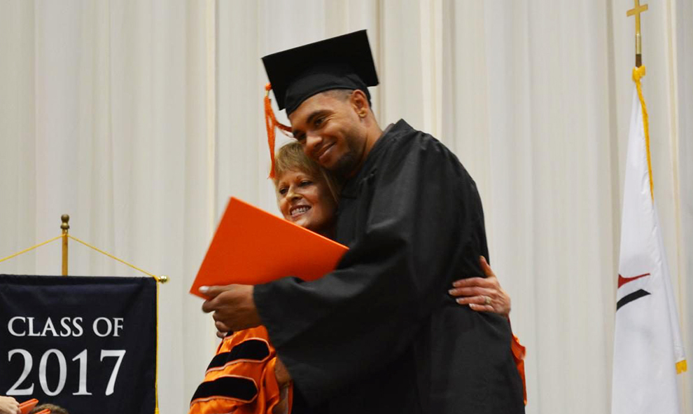 Birdsong Warren III hugs Dr. Lynne Murray after being handed his diploma.