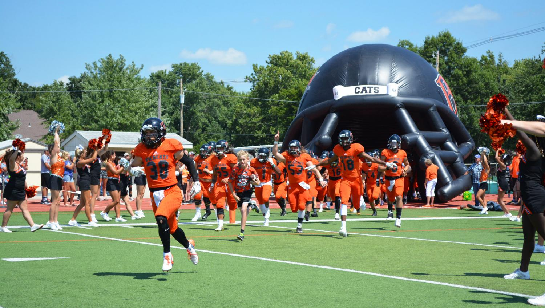 Senior Hayden Jenkins leads the Wildcats onto the field on Aug. 26.