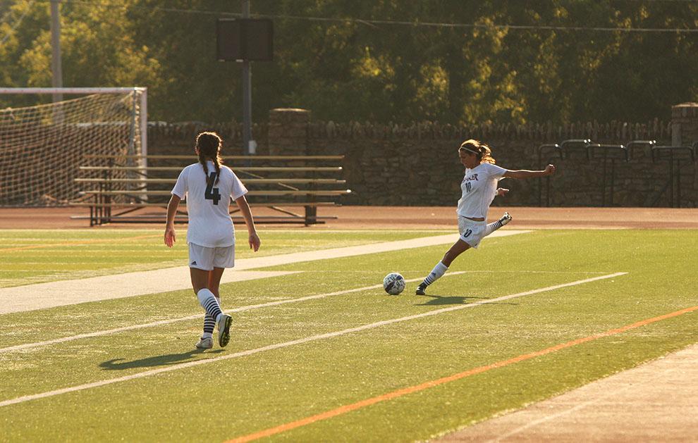 Junior Maria Flores Tome kicks the ball back into play.