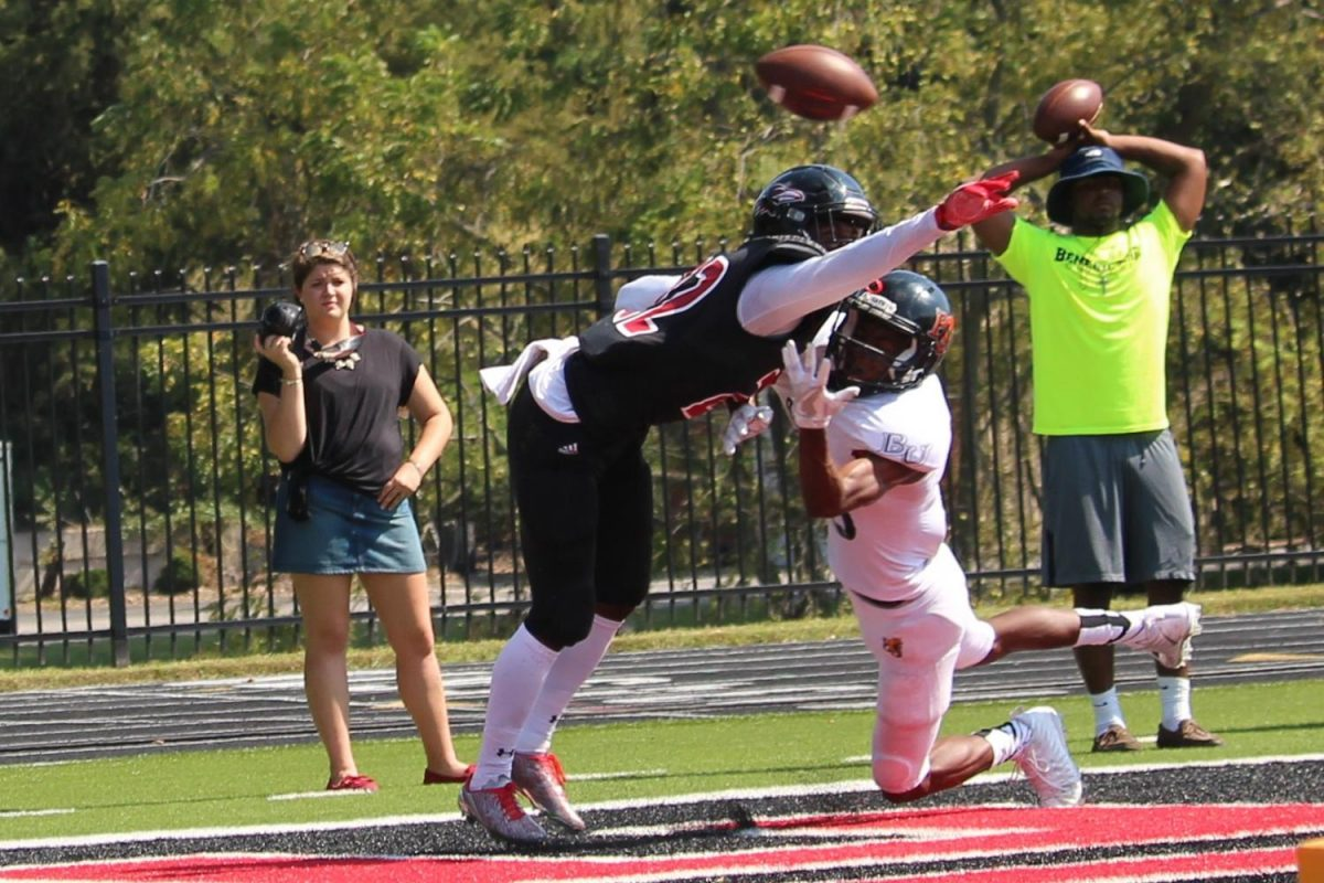 Sophomore wide receiver Tywon Moss attempts to catch the football but is blocked by Raven's defensive back Daishon Johnson. Moss had three catches for thirty-one yards and one touchdown for the Wildcats' win.
