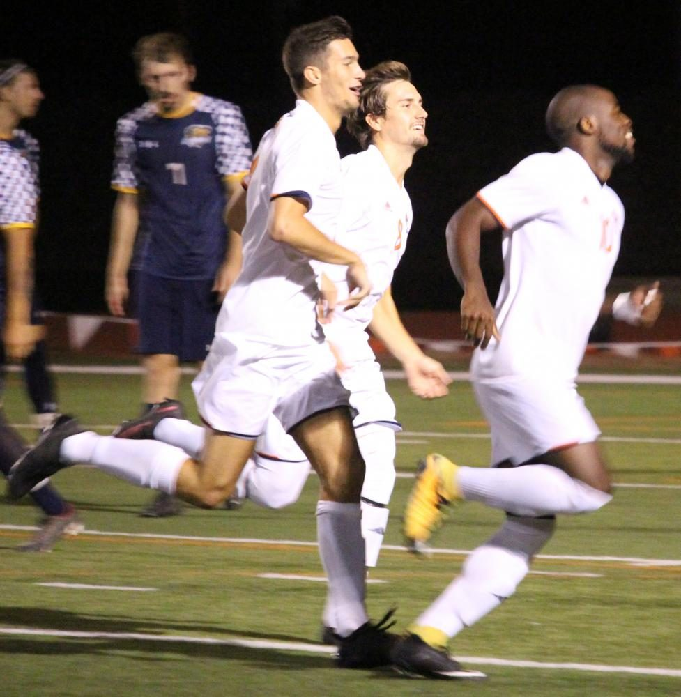 Austin Halsey and Joe Houlihan smile after teammate, Steeve Pouna, made a goal within five minutes of the men's soccer game starting.