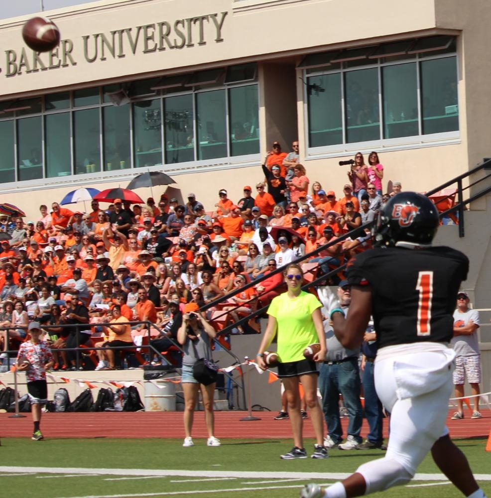 With the crowd watching in anticipation, freshman JD Woods prepares to catch a successful pass for Baker University's first touchdown during the game against Graceland University on Saturday.
