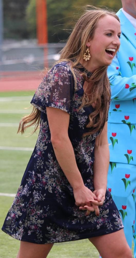 Surprised, senior homecoming candidate, Madeline McCrary, walks to receive her crown and sash during the halftime homecoming coronation.