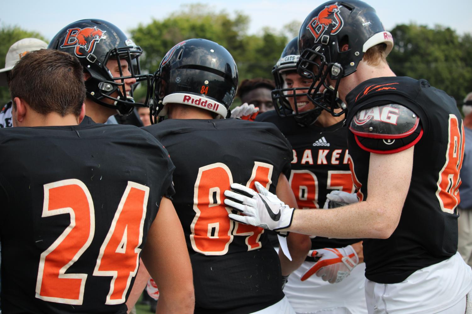 Teammates congratulate freshman Nick Snider after a play during Baker's homecoming game against Graceland University.