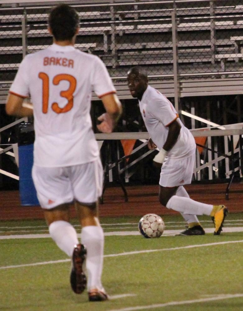 Junior Steeve Pouna searches for a teammate to pass to during Saturday night's game against Clarke University.