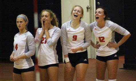 Freshmen Megan Milroy and Morgan Thomas, senior Michelle Tennant, and junior Gabby Miller laugh and cheer together from the sidelines. The game took place in the Collins Center on Sept. 26.