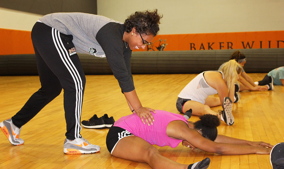 Senior Michaela Jamison helps stretch out dance team captain senior Nia Madison during practice.