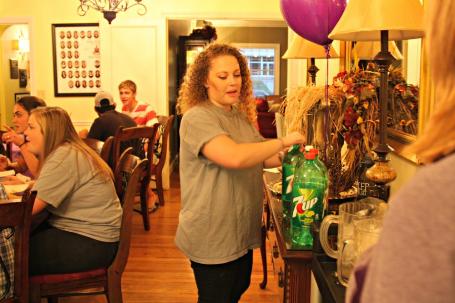 Senior Annie Hanson, member of Alpha Chi Omega, pours herself a glass, and greets guests all evening.