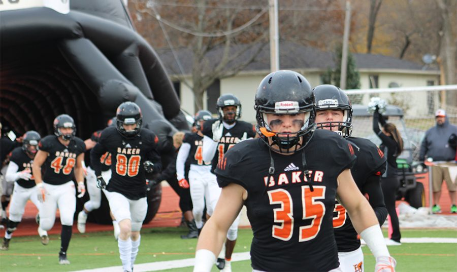 Freshman Justin Howard and teammates run out of the inflatable football helmet prior to the first round of the NAIA playoff games on Nov. 18.  President Lynne Murray offered the first 100 students free admission through the gate. The Wildcats lost to Georgetown 36-33.