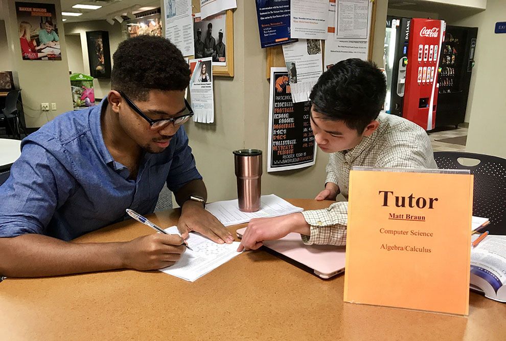 Junior Matt Braun assists freshman Johnny Lee with homework Nov. 27. Braun is a tutor in Computer Science, Algebra and Calculus.