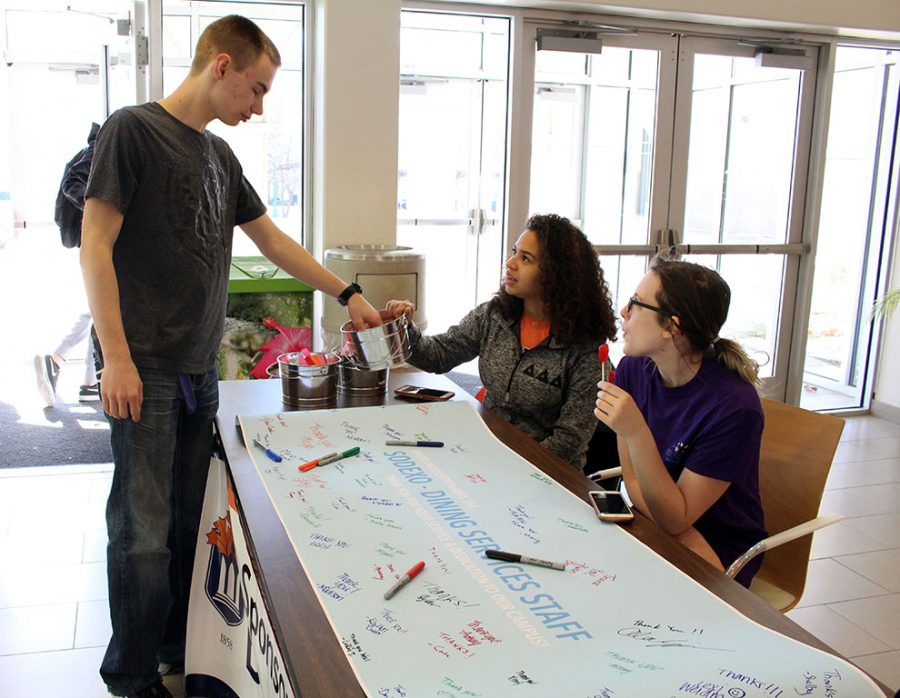 Freshman Brett Baker grabs a random act of kindness from Baker Serves members in the Harter Union on Feb. 12. Baker Serves is having students sign a Thank You banner for Sodexo as apart of Appreciation Month.