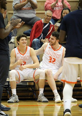 Senior Dan Young pats his teammate senior Nate Guscott on the back prior to announcing him for the starting line up. Young and Guscott are both from Australia and have played basketball at Baker together the past four years.