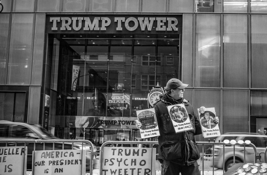 A man protests across the street from Trump Tower on March 8. Despite the dreary weather, the man stood there for awhile and held three signs while other signs and buttons were scattered around him. All of the signs condemned Trump or insulted him in some way. Several passerby's would stop and take photos in front of the Tower, most of the time to either flip off the building or do something equally as negative to express their feelings about the current president.