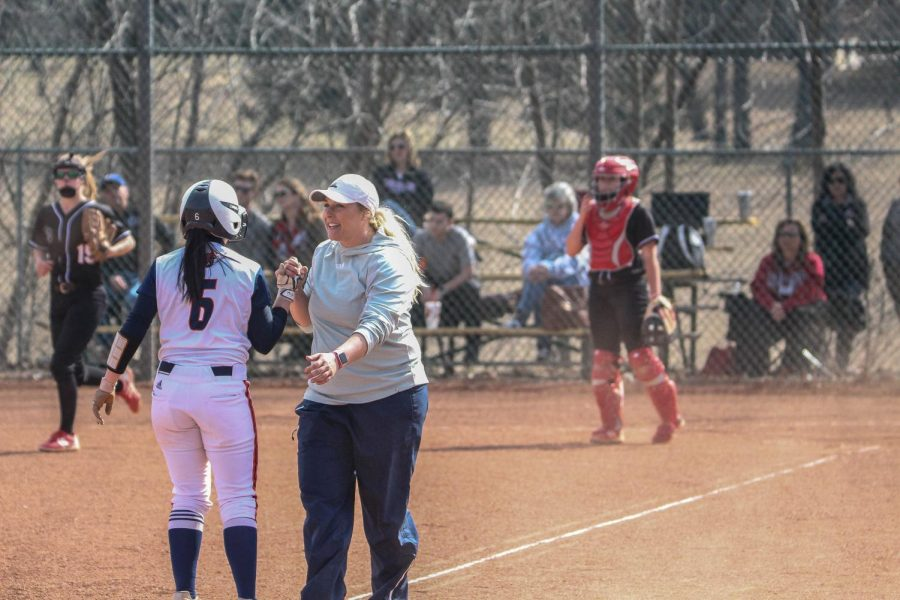 Head coach, Jamie Stanclift high-fives sophomore Hannah Flynn after a close play at third base during the Wildcats matchup again Benedictine.