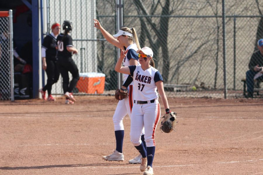Stephanie Cardona and Olivia Brees signal two outs to the outfield after an infield play against Benedictine at Cavaness Field.