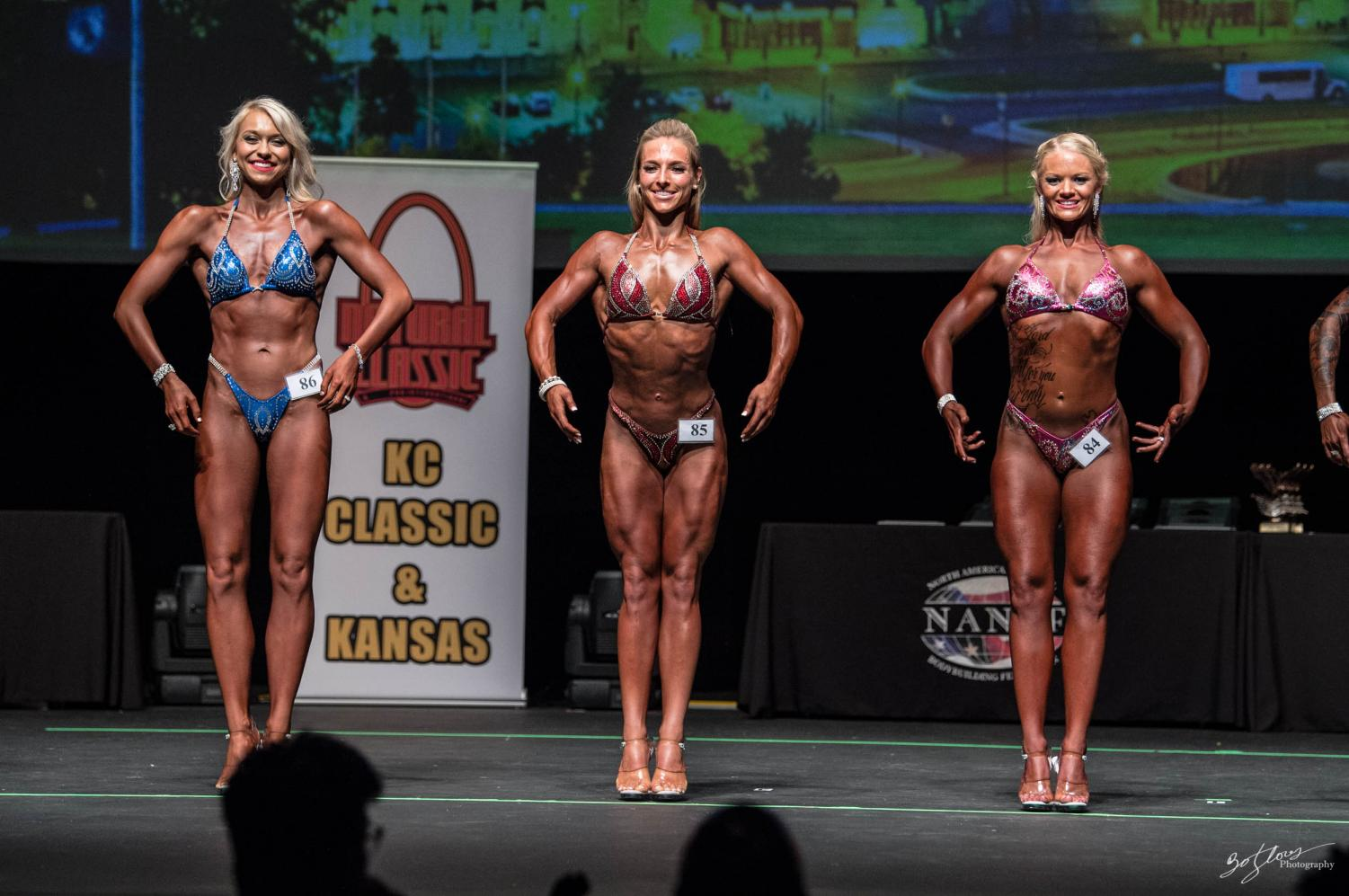 Swickard (middle) stands on stage displaying her figure to the judges and crowd.