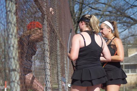 Baker's No. 2 doubles team of senior Holly Chestnut and junior Sophie Robertson talk with assistant coach Lexi Hertling between games on Monday. The doubles team picked up a win over Missouri Valley College 8-5