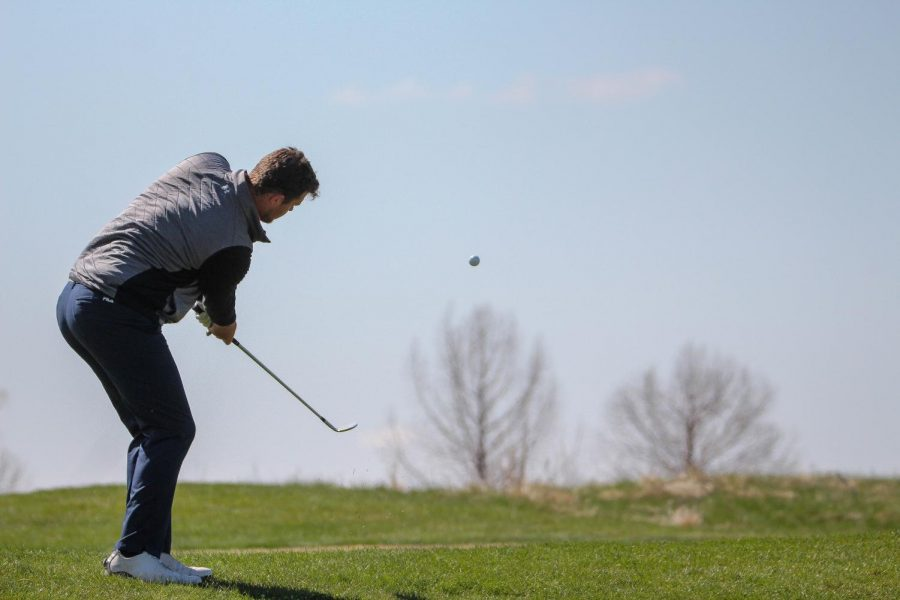Senior Riley Kemmer watches closely as he finishes a chip shot during the Spring Invitational at Eagle Bend golf course in Lawrence, Ks