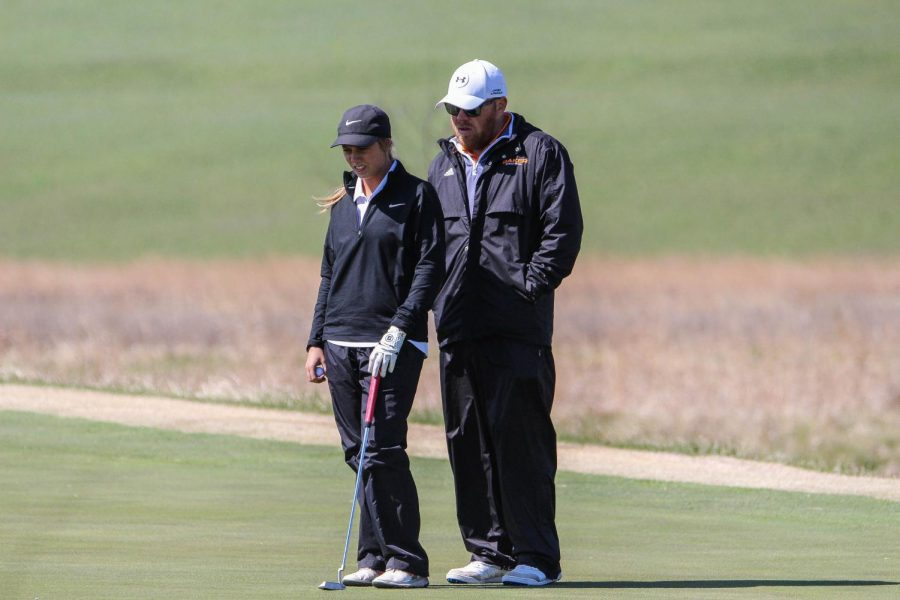 Sophomore Hannah Daugherty and assistant coach Andy Kelley look over the green and Daugherty prepares for a birdie putt.