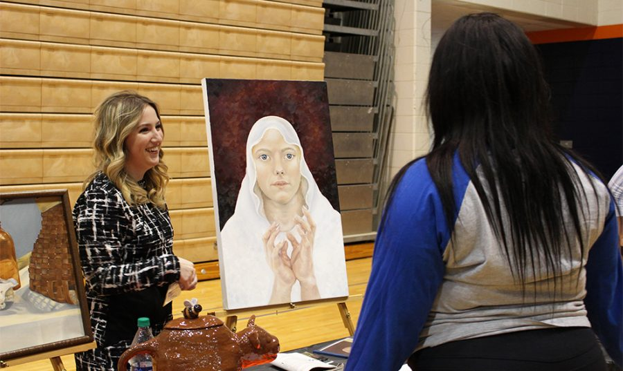 Sophomore Erynne Jamison presents her artwork to Junior Aradaisia Walker at Dialogos on April 18. Dialogos takes place in Collins Center every year where students present and are awarded scholarships. There is no class the day of Dialogos to allow students to attend this event during the day.
