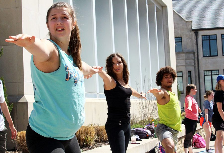 Freshmen Gretchen Boxberger (left) and Natalie Moussa (middle) and sophomore Bryson Wesley (right) perform the warrior pose at Power Yoga on April 24. The event was hosted by ESSA and Exercise is Medicine