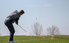 Senior Riley Kemmer watches closely as he finishes a chip shot during the Baker Spring Invitational at Eagle Bend Golf Course on April 19. Kemmer tied for second place with rounds of 76, 75 and 72, just one stroke above the tournament champion.