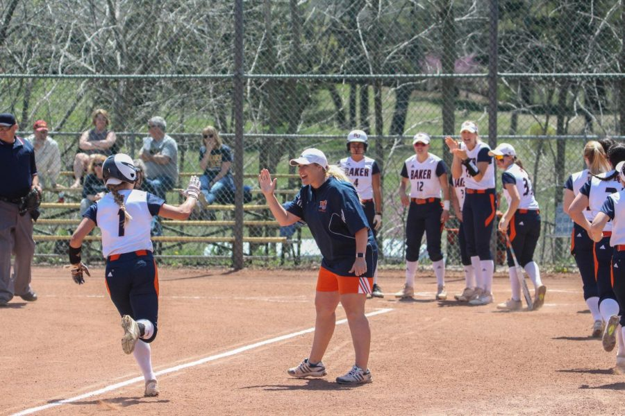 Center fielder Riley Swickard high fives head coach Jamie Stanclift as her teammates wait to celebrate after a home run. The Wildcats went on to win 13-0 over Clarke University.