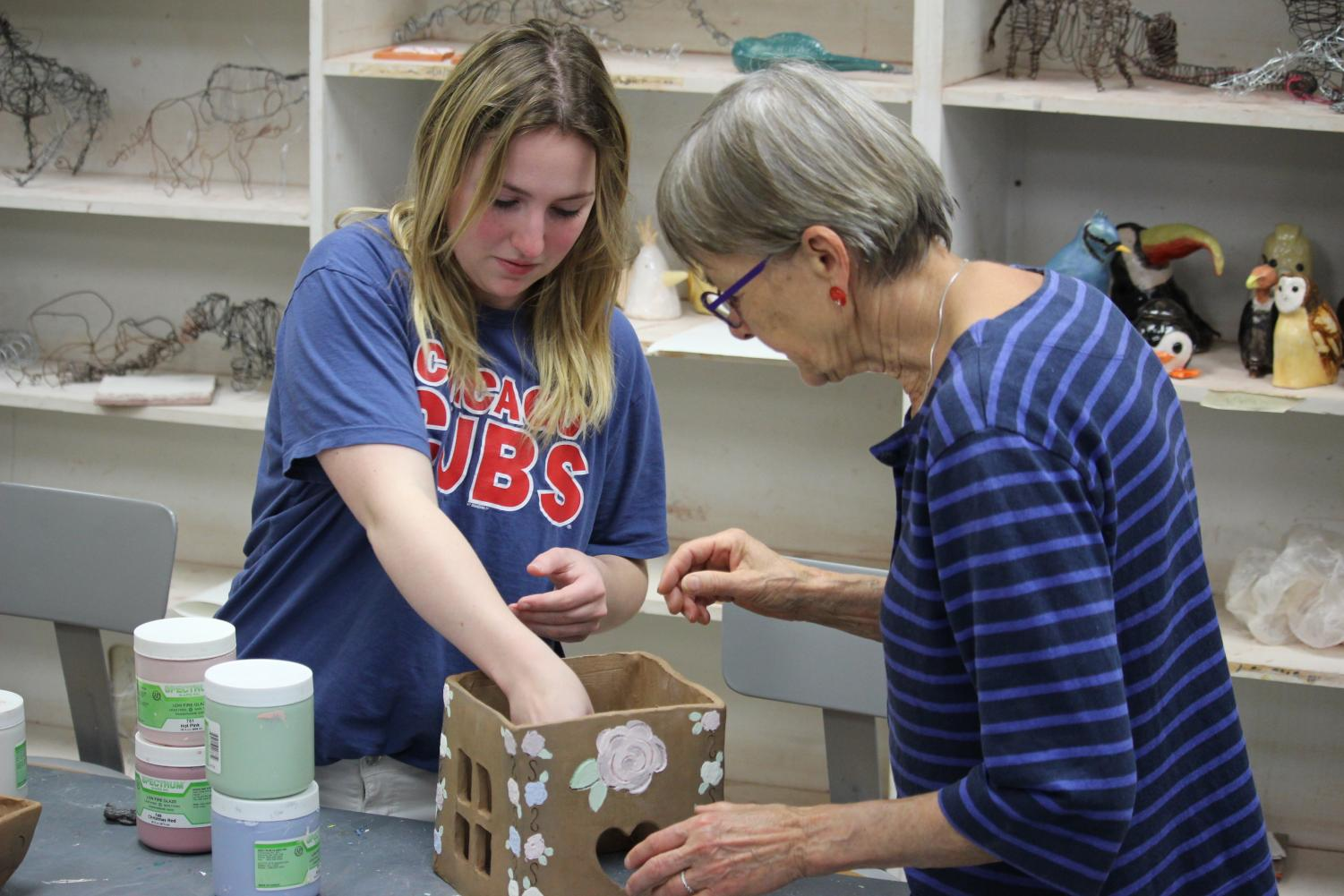Sophomore Erynne Jamison works on her ceramic birdhouse with the assistance of Professor Inge Balch.Balch spends several hours a day in the Bennett Art building teaching and firing students pieces