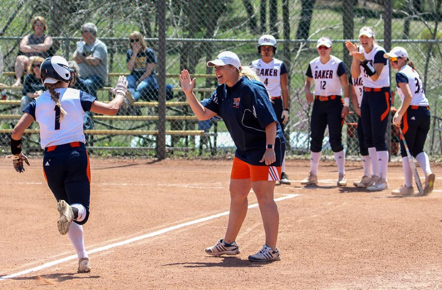 Center+fielder+Riley+Swickard+high+fives+head+coach+Jamie+Stanclift+as+her+teammates+wait+to+celebrate+after+a+home+run.+The+Wildcats+went+on+to+win+13-0+over+Clarke+University.