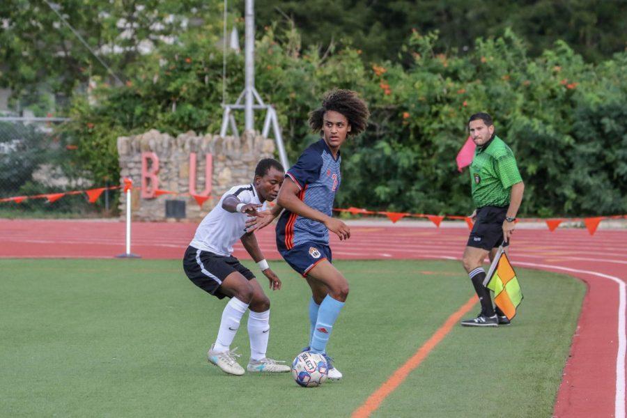 Freshman Jordan Alonge looks behind him for an open teammate as he avoids a defender down the sideline.