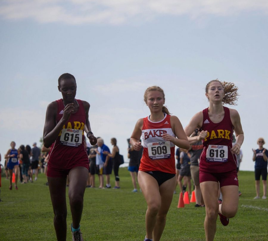 Sophomore Camille Henderson runs with determination as she passes two Park University runners at the ZK Maple Leaf Invitational.