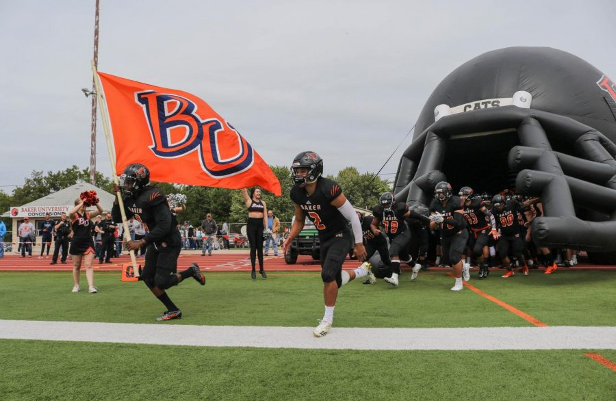 Senior Cornell Brown and Mikeice Adams lead the Wildcats onto the field against Benedictine College.