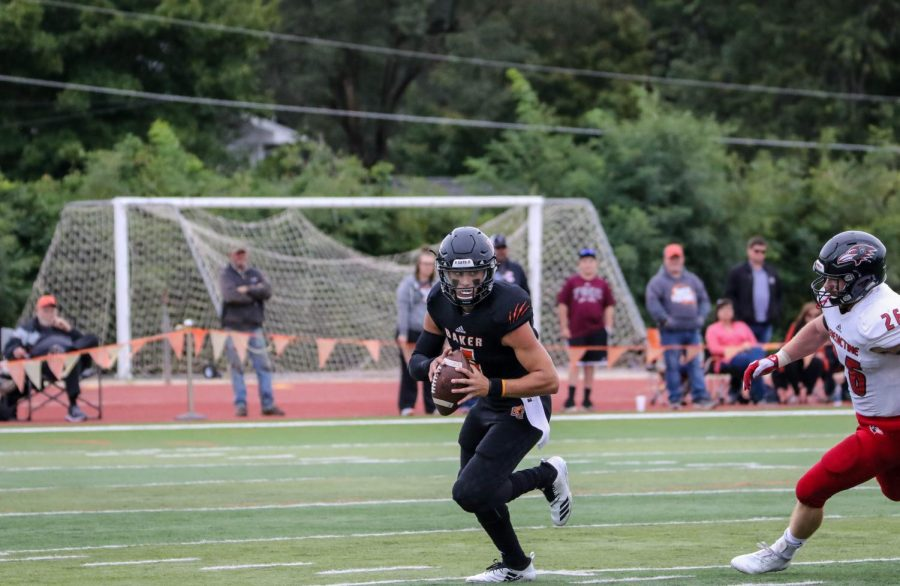 Junior quarterback Brandon Mueller scrambles away from a defender while looking for an open receiver. Mueller kept the ball and ran for the first down against Benedictine.