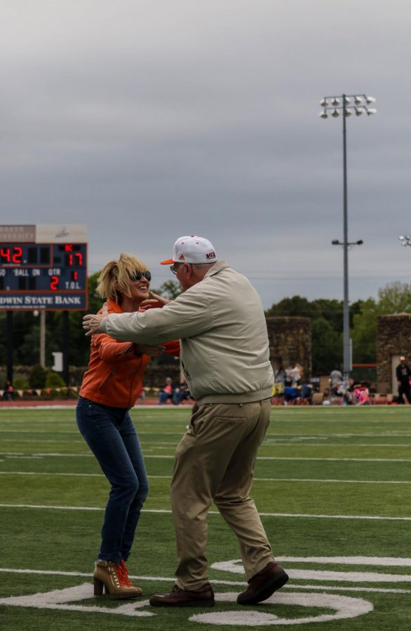 President Lynne Murray and Tom Hedrick, voice of the Wildcats, embrace in a hug at the Hall of Fame ceremony during halftime at the homecoming game.