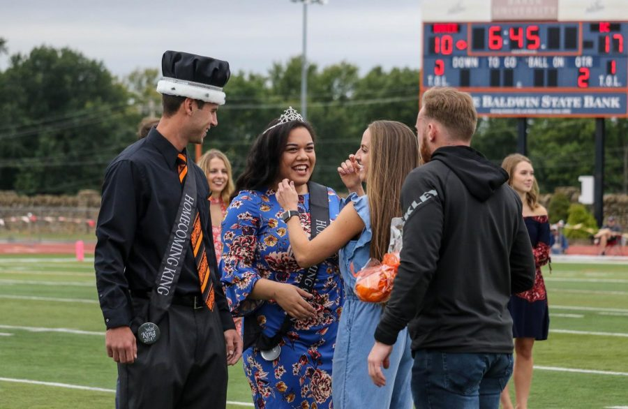 Homecoming King senior Weston Gloss and Queen senior Lela Hautau are all smiles as they receive the crown and tiara from the 2017-2018 winners, Logan Brettell and Madeline McCrary.