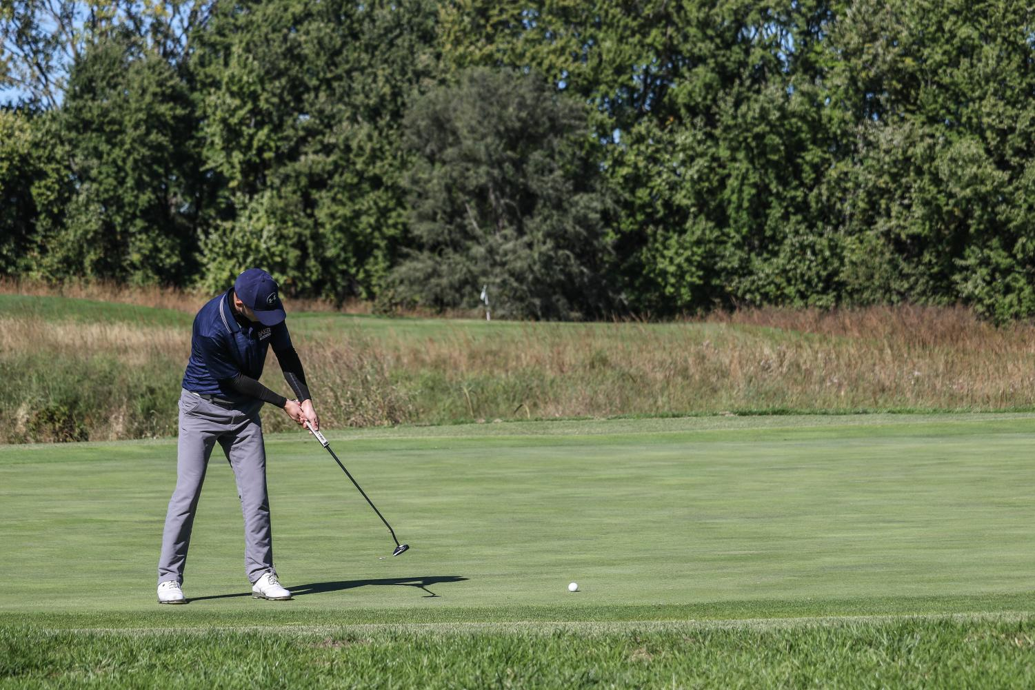 Cole Briggs hits a putt for birdie on the 3rd hole. Briggs recorded an 80 during round one of the Baker Invitational at Eagle Bend golf course in Lawrence.