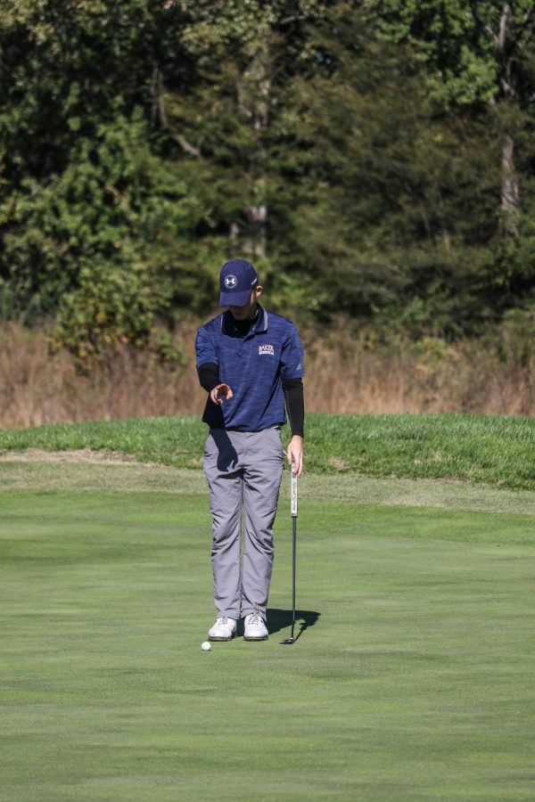 Junior Cole Briggs uses his hands to help read the green for an upcoming putt. Briggs made the putt for par during the Baker Invitational at Eagle Bend golf course in Lawrence.