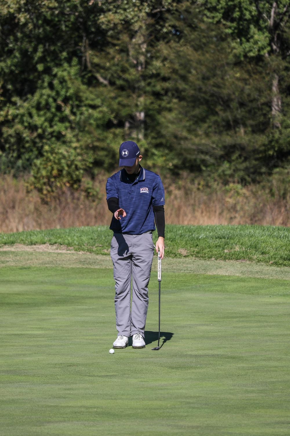 Junior+Cole+Briggs+uses+his+hands+to+help+read+the+green+for+an+upcoming+putt.+Briggs+made+the+putt+for+par+during+the+Baker+Invitational+at+Eagle+Bend+golf+course+in+Lawrence.+