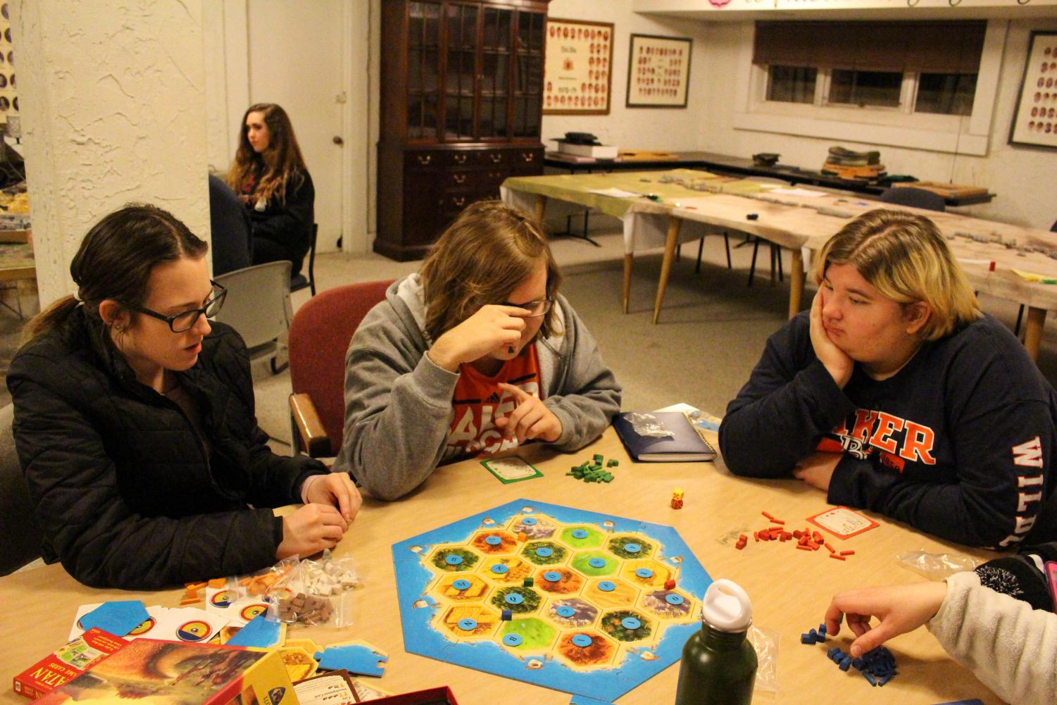 Sophomore Carly Hassenstab, Freshman Chance Prosser and Sophomore Kaycee Bauer, play Settlers of Catan, one of the many games offered at BUGS. Catan is an analytical game that challenges players to settle different lands and produce civilizations.