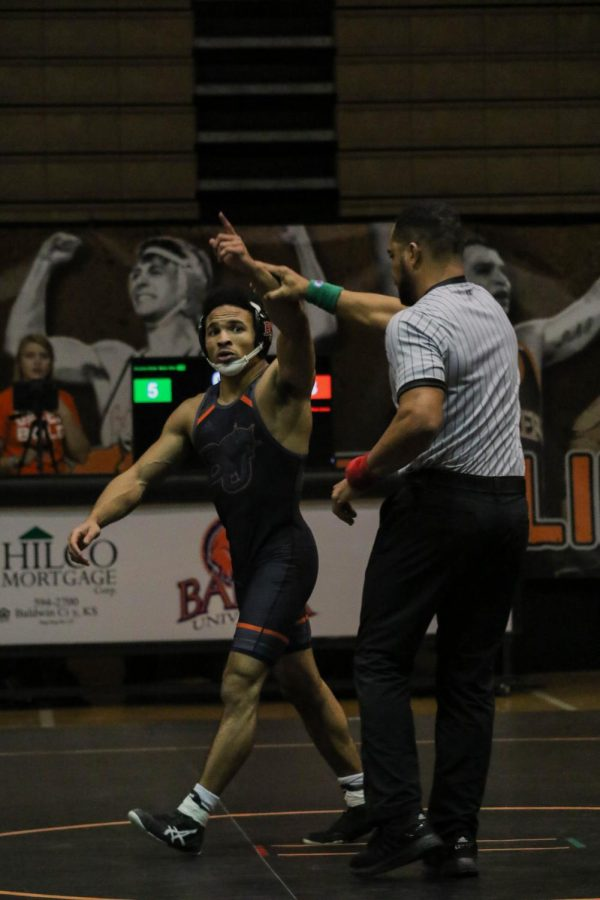 Senior Brandon Dofat points to the crowd in celebration as his hand is raised after a 6-3 decision over Gilberton Rodriguez of William Penn.