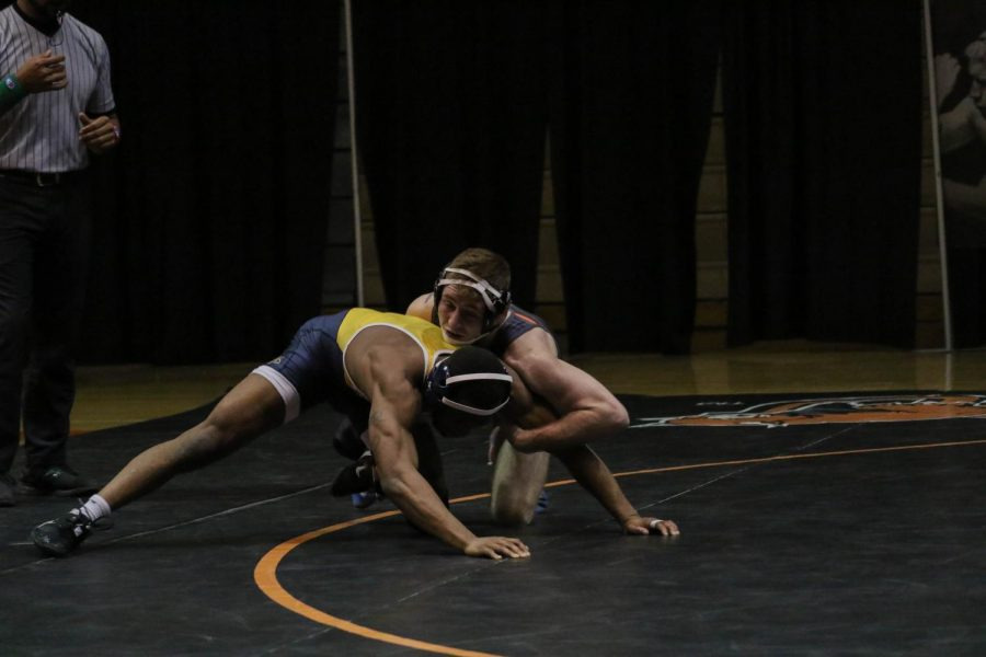 Colby Johnson, who is ranked 11th in the country at the 149-pound weight class, finishes a takedown during his match against William Penn. Johnson would rally to a 14-1 major decision, earning the Wildcats four team points.