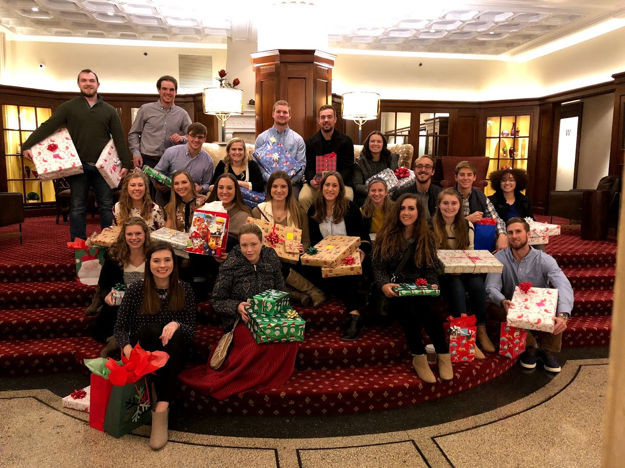 "The parMentors pose with gifts purchased for the ""Adopt-a-Family"" project. The items were wrapped at the Eldridge Hotel following the group dinner."
