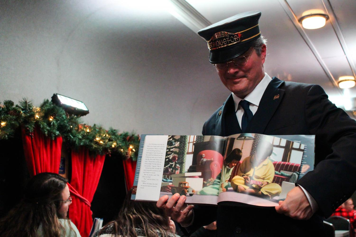 "The train conductor walks up and down the aisle of the train while a narration of ""The Polar Express"" story book is played over a speaker."