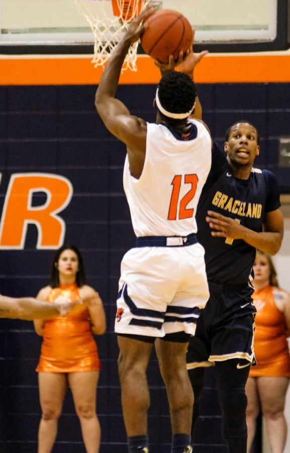 Junior Charles Fisher goes up for a shot against Graceland defender. The Cats lose 74-88.