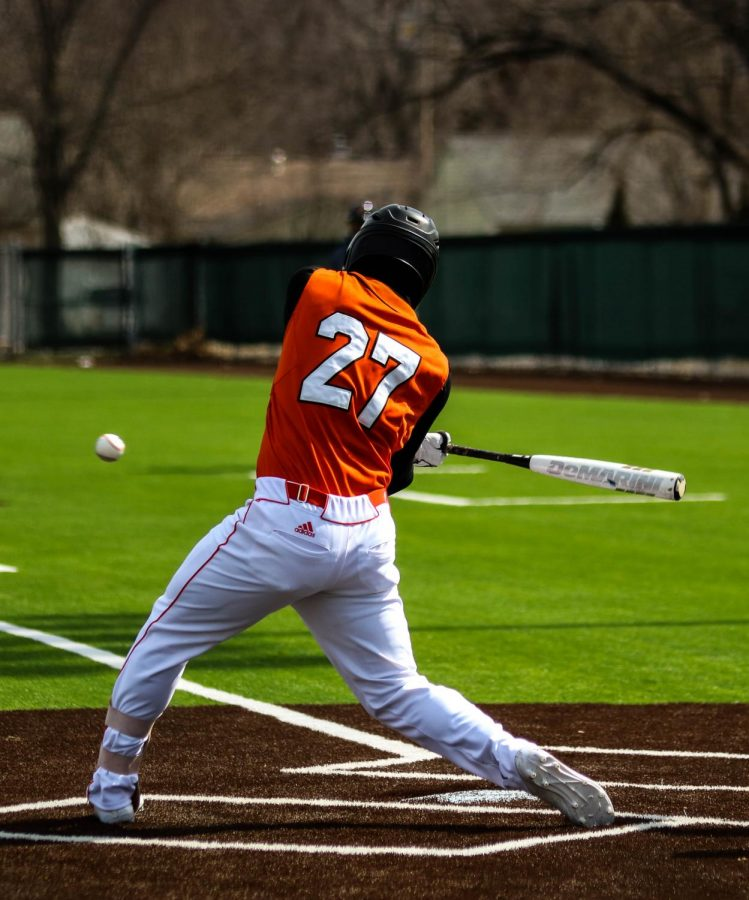 Wyatt Logan, Senior, drives a ball to center field against Clark University.